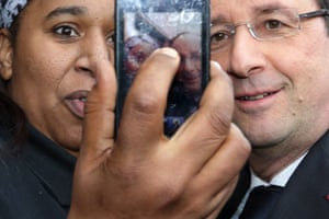 A woman takes her picture with François Hollande as the French president visits Gresilles, in the Socialist stronghold of Dijon.
