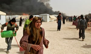Syrian refugees run from a gas explosion at the Za'atari Syrian refugee camp in Jordan.