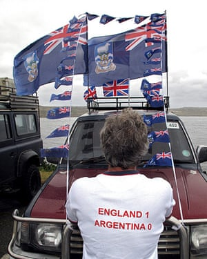 Falkland Islands: A man looks at a vehicle decorated with flags in Stanley