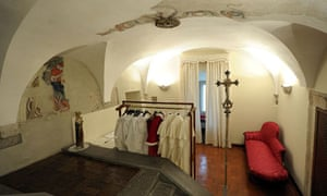 Different sizes of papal vestments hang ready for use at the Sistine Chapel