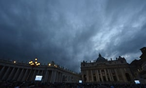 People gather in St Peter's Square watching giant screens showing the chimney on the roof