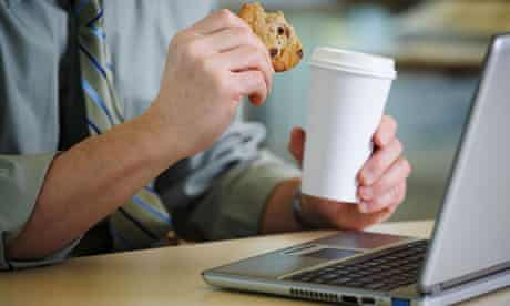 Man at desk with coffee and a cookie