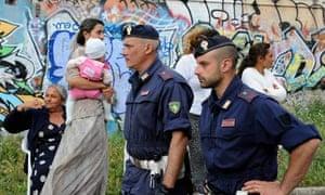 Italian policemen patrol a Rom's camp at