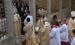 Pope Francis, cross in hand, leaves the Sistine Chapel.