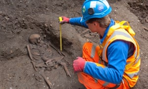 A photograph released by Crossrail on today shows an archeologist measuring a skeleton found during a excavation of a tunnel construction supporting shaft at a site in Farringdon, London. So far thirteen skeletons have been found and are believed to date from the time of the Black Death in the mid-14th century.