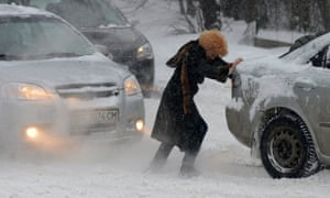 A woman pushes a jammed car as heavy snow falls in Lviv, Ukraine.