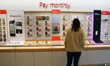 Customer Looking At Monthly Contract Mobile Phones In Vodaphone Shop Surrey England