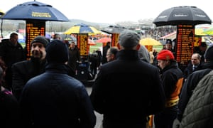 It's been freezing there all week, now the umbrellas are up as punters check out the odds during Cheltenham Gold Cup Day at the Cheltenham racecourse.