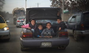Afghan boys peer out of the boot of a car as they get a ride through the center of Kabul.