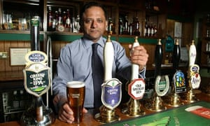 Rooney Anand, CEO, Greene King, behind bar