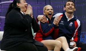 Alexa Scimeca and Chris Knierim of the U.S. react to their score with coach Dalilah Sappenfield after performing their free skating program at the ISU World Figure Skating Championships in London, Canada.