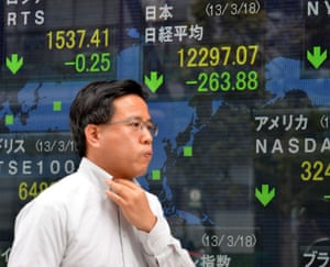 A businessman passes before a share prices board in Tokyo on March 18, 2013.