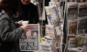 A member of the public selects a newspaper from a news stand in London