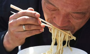 A Chinese man eats noodles with disposable chopsticks at a restaurant in Beijing