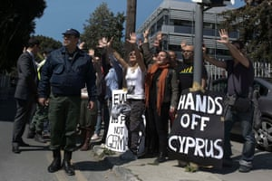 Demonstrators raise their arms in protest as Cypriot President Nicos Anastasiades's convoy drives to the parliament in Nicosia March 18, 2013.