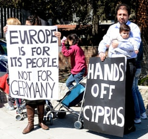 People hold a banners infront of the Cypriot parliament in Nicosia, Cyprus, 18 March 2013.