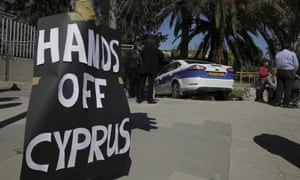 "A sign which reads ""Hands off Cyprus"" is plastered on an electricity pole outside the pariament building in the Cypriot capital Nicosia on March 18, 2013."