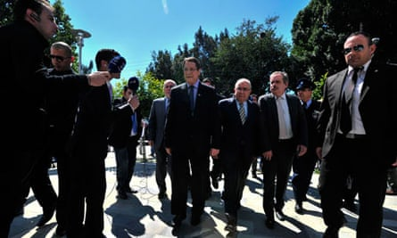 Cypriot President Nicos Anastasiades (C) arrives at the parliament in Nicosia