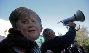 A protester wearing a mask of German Chancellor Angela Merkel takes part in an anti-bailout rally outside the parliament in Nicosia  March 18, 2013.
