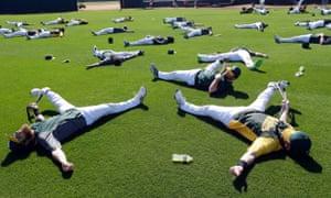 奥克兰田径运动员在凤凰城的西雅图水手队参加春季训练棒球比赛前进行瑜伽练习。
