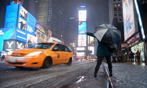 A woman tries, unsuccessfully, to hail a taxi cab during a snowstorm in Times Square in New York.