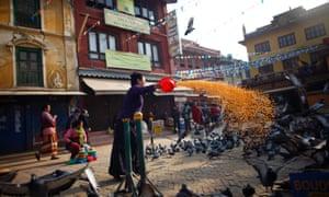 A Nepalese Buddhist woman feeds pigeons near the Boudhanath Stupa in Katmandu, Nepal.