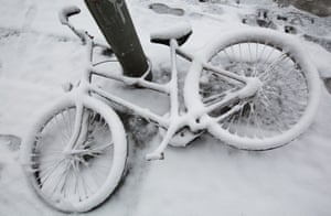 Fresh snow covers a bicycle on the ground in Berlin, Germany.