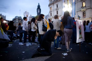 As people watch Pope Francis' inaugural Mass on a big screen outside the Metropolitan Cathedral in Buenos Aires, Argentina, one member of the audience prays.
