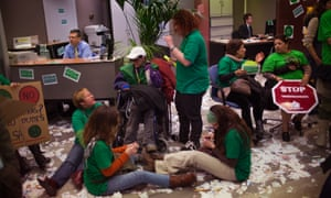 Bank employees work at their desks, as members of the Mortgage Victims' Platform occupy a branch during a protest to support neighbors who are threatened with eviction, in Barcelona, Spain.