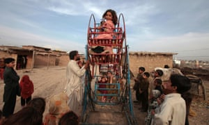 An Afghan girl smiles as she rides on a hand-operated ferris wheel with other children in a slum on the outskirts of Islamabad.