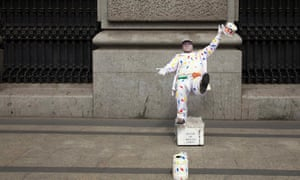 A street artist dressed as a painter, performs on the pavement in central Madrid, Spain.