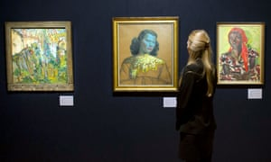 """A gallery assistant at Bonhams auction house, London, looks at """"Chinese Girl"""" by Vladimir Tretchikoff. The painting is his most iconic work, and is said to be the most widely reproduced and recognisable picture in the world."""