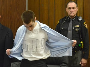 """T. J. Lane takes off his shirt to show a white t-shirt with the words """"Killer"""" spelled out at his sentencing before Geauga County Judge, David Fuhry, in Cleveland, Ohio. Lane was sentenced to life without parole for killing three students in a shooting rampage at a high school in a small town east of Cleveland."""