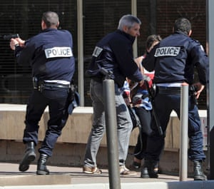 French policemen and special forces safeguard a hostage at the scene where a man had shot dead a dentist and taken hostages in a medical clinic in Marseille.