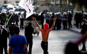 Bahraini anti-government protesters demonstrate in front of a cordon of riot police in Bilad al-Qadeem, Bahrain. Clashes erupted after police dispersed a protest held to mark the anniversary of the death of the protester, Hani Abdel Aziz. Photograph: Hasan Jamali/AP