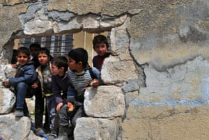 Syrian children look out from a hole in a wall during a funeral ceremony of a Syrian army soldier who was killed as he tried to defect, in Azmarin village, in the northwestern province of Idlib. The conflict has killed at least 70,000 people, and forced more than one million Syrians to seek refuge abroad.