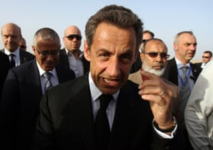 Former French president Nicolas Sarkozy walks amidst French and Libyan officials as he arrives in Benghazi to attend a military parade to celebrate the second anniversary of NATO's first military operation in Libya.