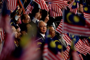 Malaysian Prime Minister Najib Razak (C) looks on as others wave the national flag before a live telecast for the National Transformation Programme Annual Report in Kuala Lumpur.