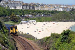 Railways: Train leaving Porthminster and Porthminster beach in St Ives ,Cornwall