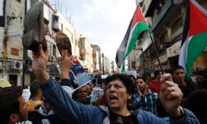 Palestinian demonstrators hold shoes and flags as they take part in a protest in the West Bank city of Ramallah on Tuesday. Palestinian police scuffled on Tuesday with scores of demonstrators protesting against the visit of US President Barack Obama to the occupied West Bank later this week.