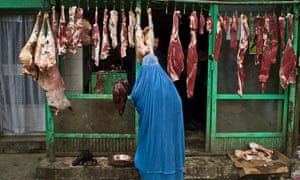 An Afghan woman buys meat at a butcher's shop a day before the celebration of the Persian New Year Nowruz in Kabul, Afghanistan.