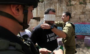 A Palestinian activist, wearing a T-shirt with Martin Luther King's famous line 'I have a dream' printed on it, is blindfolded by Israeli soldiers during a protest against US President Barack Obama's visit to the region, in the West Bank town of Hebron.