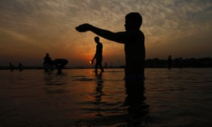 A Hindu devotee performs rituals as others bathe in the River Ganges, in Allahabad, India.