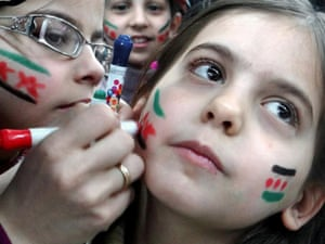 In an image provided by Aleppo Media Center AMC which has been authenticated based on its contents and other AP reporting, Syrian girls paint their faces with colors of the Syrian revolutionary flag during a fesitval, in Aleppo.