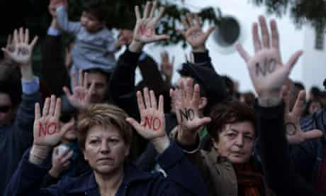 """Cypriots show their palms reading """"No"""" d"""
