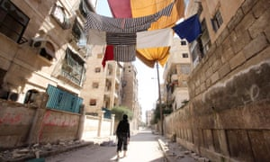 A Free Syrian Army fighter walks along a street in Aleppo's Saif al-Dawla district. Curtains and other fabrics are hung as protection from snipers loyal to Syria's President Bashar al-Assad.