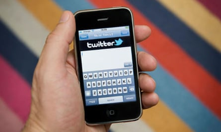 Male hand holding an iPhone about to tweet