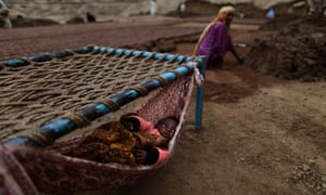 A Pakistani child, lies in a hammock as her mother makes bricks, at a brick factory in Mandra, near Rawalpindi.