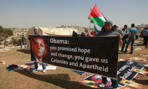 Palestinian activists hold posters with the photo of US President Barack Obama near newly-erected tents in an area known as E1 near the settlement of Ma'aleh Adumim, near Jerusalem.