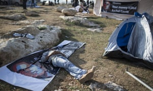 A man sleeps on a Obama poster at a protest camp in the E1 area next to Ma'ale Adumim.
